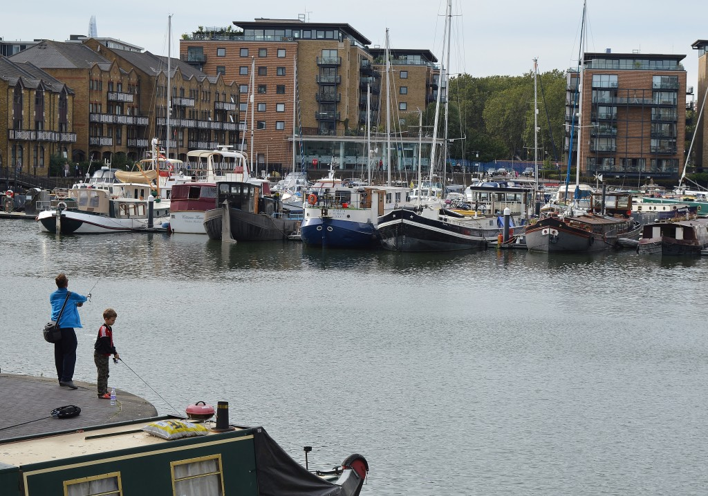 Father and son fishing off the side of Limehouse Basin